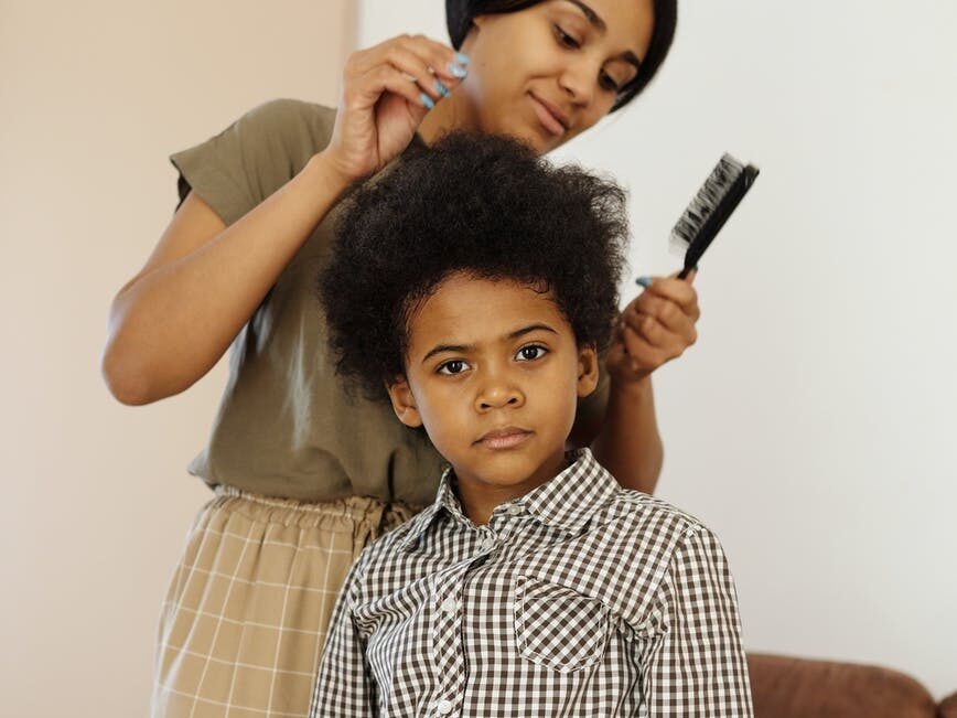 mother fixing her son s hair